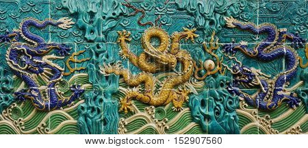 TILES OF DRAGON SCULPTURES ON THE WALL
