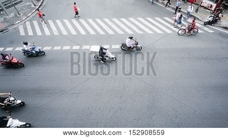 street on the top view with people are going acroos crosswalk sign on the road and car and motorcycle (Aerial photo)