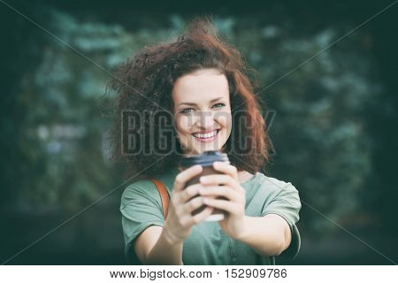 Happy young woman with cup of coffee outdoor