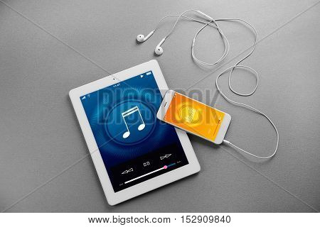 Tablet, smartphone and earphones on gray background. Music player interface on screen.
