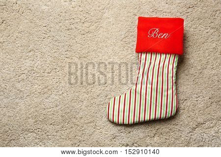 Cute Christmas stocking on beige textured background