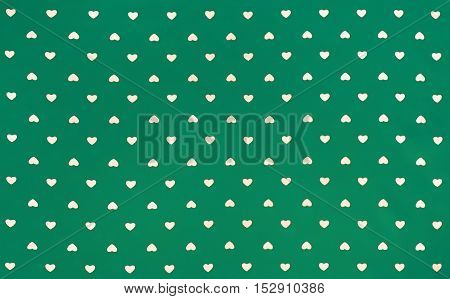 Green Fabric cloth with white hearts pattern, texture, background, retro style. Place your text or design.