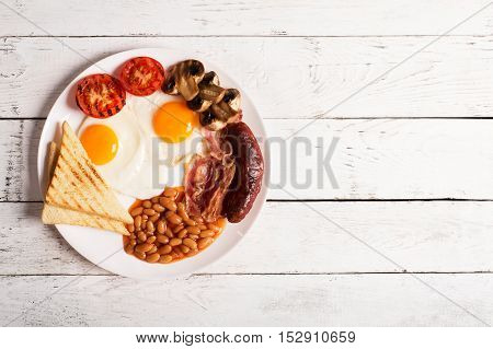 English breakfast prepared with two fried eggs, beans in tomato sauce, grilled tomatoes, mushrooms, bacon and toasts. Meal on a white wooden table with copy space
