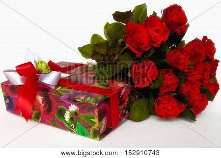 Gift in a beautiful box and flowers ,festive red background