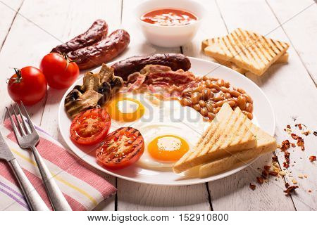 English breakfast prepared with two fried eggs, beans in tomato sauce, grilled tomatoes, mushrooms, bacon and toasts. Meal on a white wooden table
