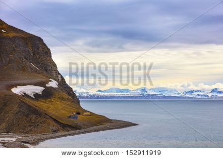 Houses in a mountain side in the arctic landscape. Clouds over mountains covered with snow in the cold arctic environment at Svalbard.