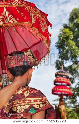 Balinese man in sarong costume hold red umbrella with traditional pattern on ceremony in hindu temple. Arts festivals in Indonesia culture of Bali island Indonesian people. Asian travel background