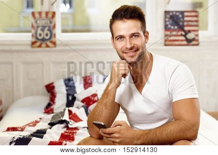 Happy young man using mobilephone in the morning, smiling, looking at camera.