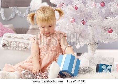 Little girl sitting under christmas tree, playing with boxes.