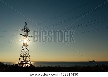 beautiful landscape with high voltage pylon near the river at the sunset. Russia, 2106.