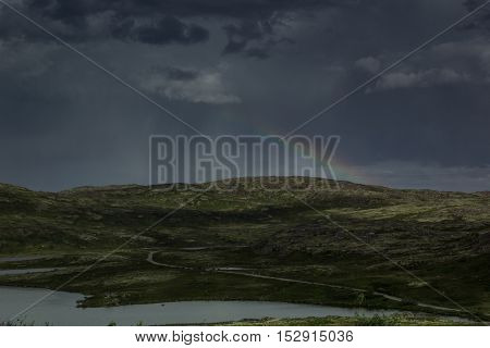 Beautiful gloomy dark stormy sky and rainbow over a green valley. Arctic summer the tundra Norway.