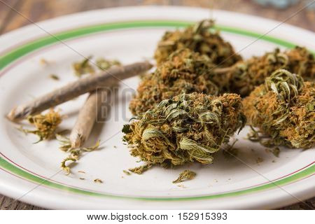 Marijuana buds and joints in the glass plate on the wooden rustic table