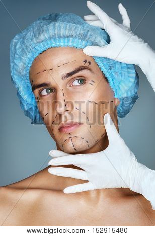Attractive man patient with guideline marks on his face before plastic surgery operation. Surgeon touching man face. Beauty face concept