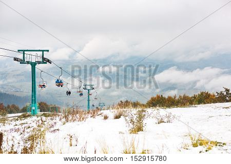 The slope of the old chairlift at a ski resort. Autumn colored trees and snow.