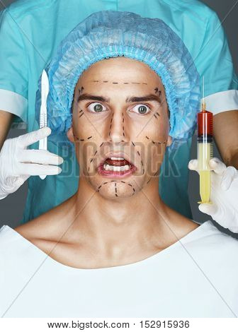 Nurse with syringe and scalpel near the face of the scared patient. Man's face in medical headwear with pencil marks on skin for cosmetic medical procedures.