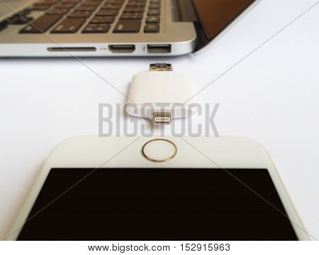 CHIANGRAI THAILAND -SEPTEMBER 7 2016: Close-up image of two way external flash storage between the Apple iPhone 6 and Apple Macbook Pro Retina on white background. Focus with USB connector.