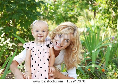 Happy mother with daughter resting in park on sunny day