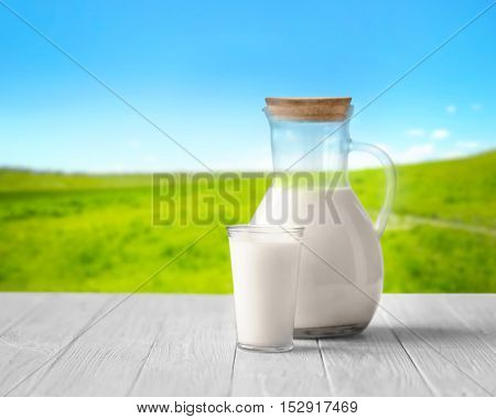 Glass and jug with milk on white wooden table against blurred nature background. Dairy concept.