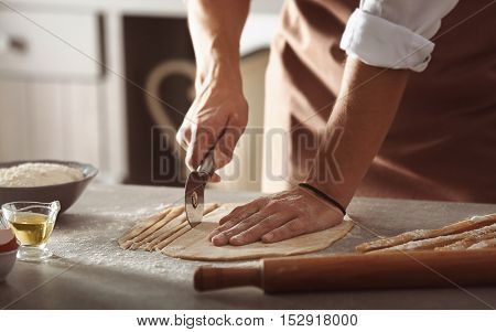Male hands preparing pasta on kitchen table