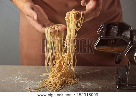 Man using pasta machine to prepare spaghetti, close up view