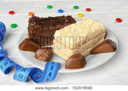 Dieting concept. Delicious sweets on a plate and measuring tape on white table