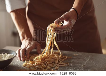 Man preparing pasta on kitchen table, close up view