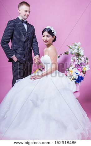Groom looking over his beautiful bride whilst she sits on a flower chair against a pink background