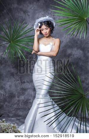 Portrait of elegant bride standing against grey wall
