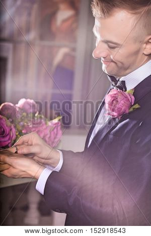 Handsome groom placing a wedding ring on brides finger