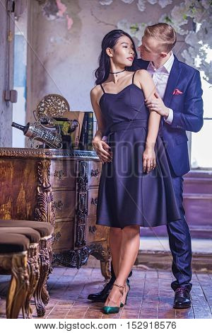 Seductive multi racial couple kissing in their living room, she is wearing a lovely black dress and he is wearing a stylish suit