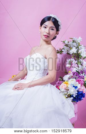 Elegant bride looking away while sitting on chair against pink background