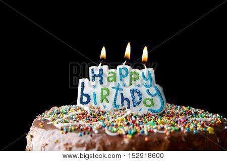 Birthday cake with greeting candles on dark background