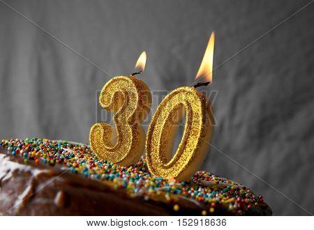 Birthday cake with burning candles on grey background