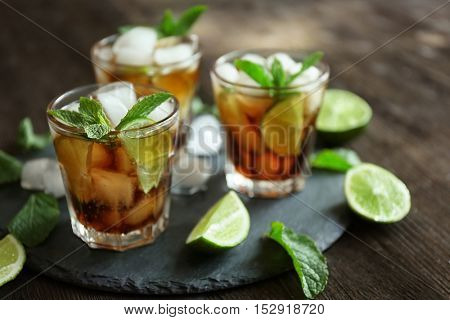 Glasses of cocktail with ice and mint on wooden table closeup