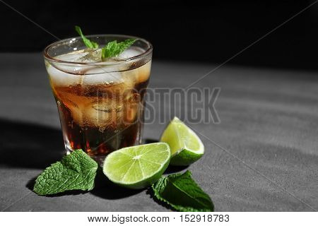 Glass of cocktail with ice, lime and mint on dark textured background