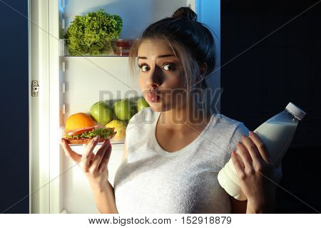 Beautiful girl eating sandwich at night. Unhealthy food concept