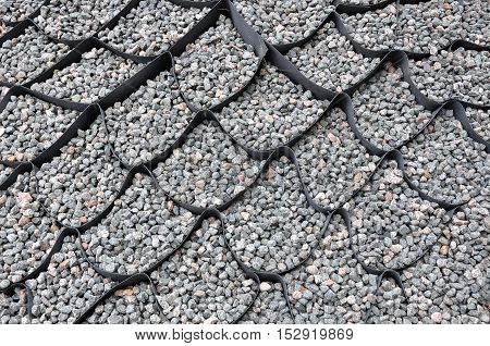 The design of the slope. Plastic black honeycomb frame filled with small natural stones closeup.