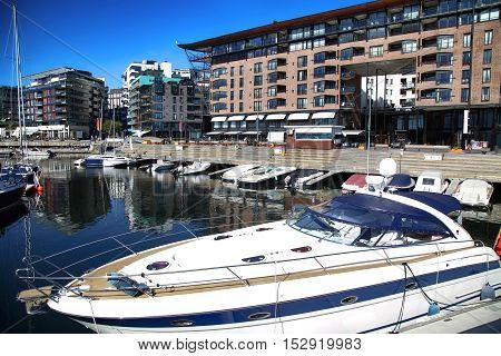 Yacht and modern district on street Stranden Aker Brygge in Oslo Norway