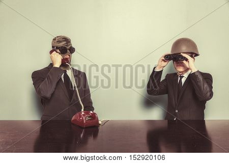 Two businessman sitting at office desk wearing glasses