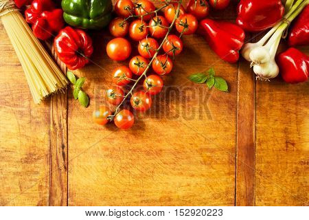 Vegetables and pasta before cooking on a wooden table with copy space, top view
