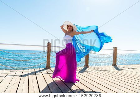 Photo of  beautiful young woman wearing hat and blue veil at sea resort