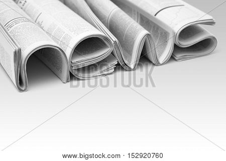 Stacks of modern newspapers composed in form of word NEWS on gradient background. Concept of news and events of company
