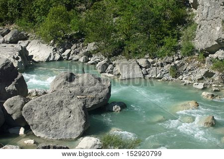 Clear pale blue fast flowing river with large rocks and rapids near the village of Rimon in the Drome valley France. Trees lining the river as background.