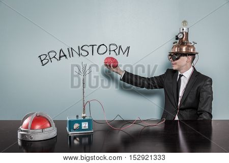 Brainstorm concept with businessman holding brain at hand in office