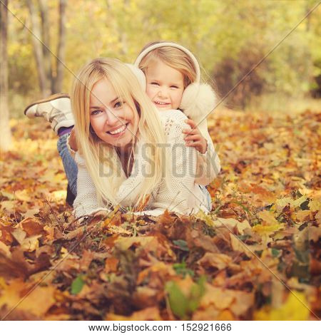 Young happy blonde mother and little girl have a fun lying on yellow maple leaves outdoor in autumn park