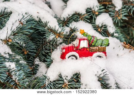 Toy Car With Christmas Tree On Snowy Branch Fir