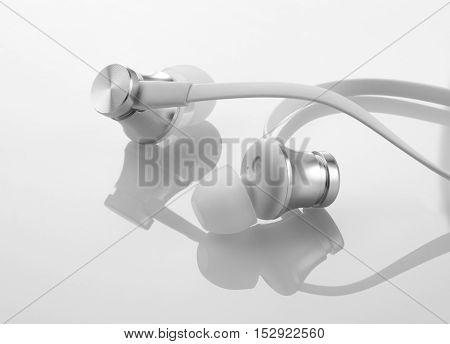 In Ear Earphones Headphones on Reflective White Background