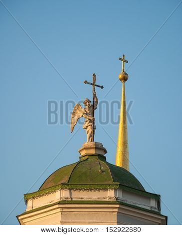 Sculpture of an angel with a cross on the steeple of the church