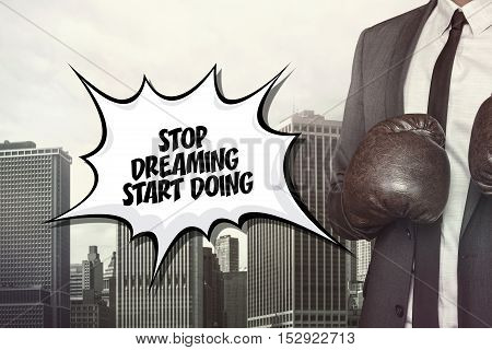 Stop dreaming text on speech bubble with businessman wearing boxing gloves