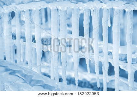 Winter background of hanging icicles after rain